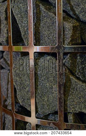 Close up of stones in pillar-model sauna heater. Vertical image.