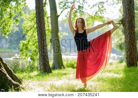 Caucasian woman in red skirt doing balance yoga asana in summer park. Hasta padangusthasana or Extended Hand To Big Toe Pose