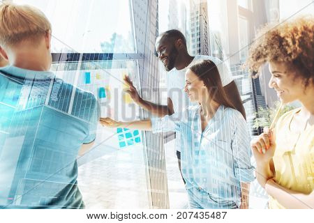 Nice idea. Waist up of young attentive colleagues standing in front of paper with sticky notes and expressing interest while working on new start up