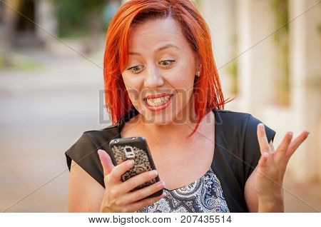 An attractive Caucasian woman learned good news, she is holding a smartphone in her hands. Cute girl receiving good news by phone. Excited student, astonishing message.