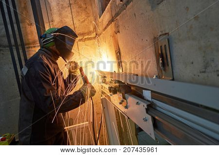 lift worker welding elevator fasteners in lift shaft