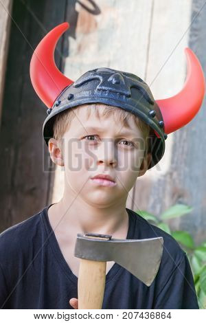Boy in a Viking helmet with horns holds an ax outdoors