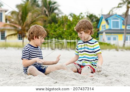 Two little kids boys having fun on tropical beach, happy best friends playing, friendship concept. Siblings brothers, twins in family look with palms on background. Family vacations on Seychelles