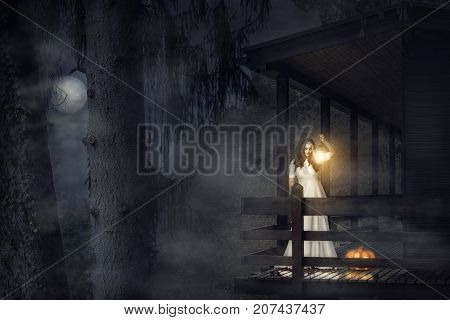 Spooky girl in a white dress holding a lit lantern a pumpkin near her on the balcony of a wooden house in a dark foggy forest under the moonlight.