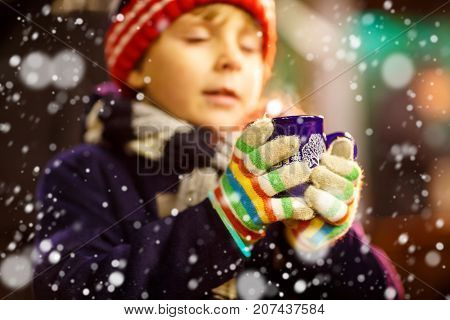 Little cute kid boy with cup of steaming hot chocolate or children punch. Happy child on Christmas market in Germany. kid in winter clothes warming hands on cup and drinking. Selective focus on cup