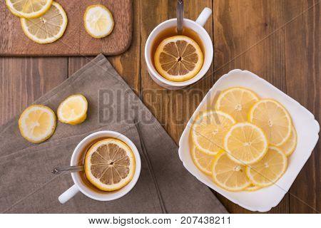 Composition with lemon tea on a wooden table shot overhead.