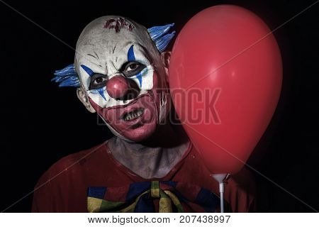 closeup of a scary evil clown wearing a dirty costume and holding a red balloon against a black background