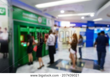 blurred image of people queuing to withdraw money from ATM (Automated Teller Machine) e-banking finance payment and shopping online concept