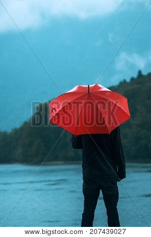 Man with red umbrella contemplates on rain in front of a lake. Sad and lonely male person looking into distance.