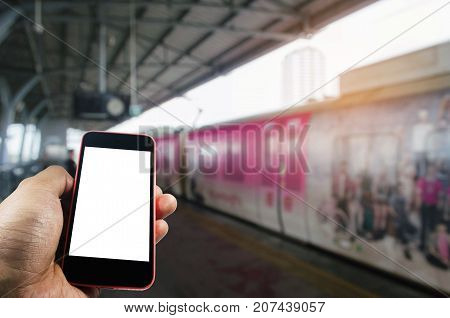 hand using smart phone isolated blank screen with blurred image of subway at railway station people lifestyle transportation technology internet network connection social media concept