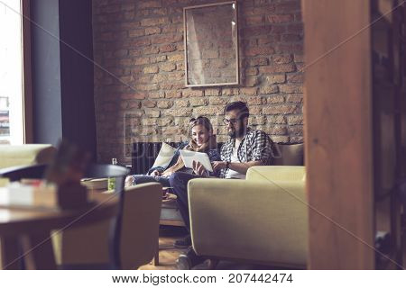 Young couple sitting in a cafe having a morning coffee surfing the web on a tablet computer and enjoying their time together