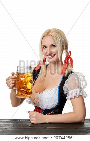 Young bavarian woman in dirndl sitting at table with beer on white background. Oktoberfest