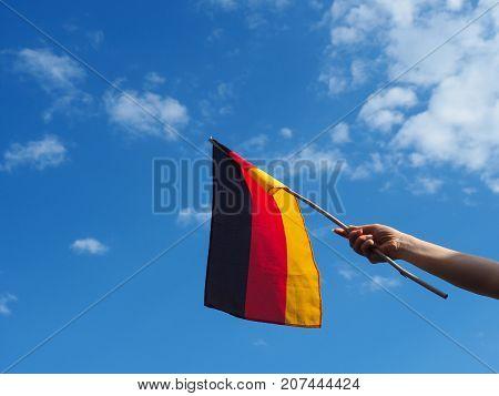 Female hand waving a German flag on a blue summer sky