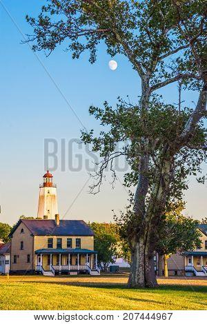 A daylight moon rises over Fort Hancock on Sandy Hook along the New Jersey coastline.