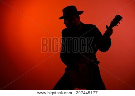Silhouette Of A Guitarist On A Red Background.