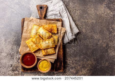 Fried cheese empanadas. Traditional Latin American snack served on wooden board with chili sauce and mustard. Top view, stone background.