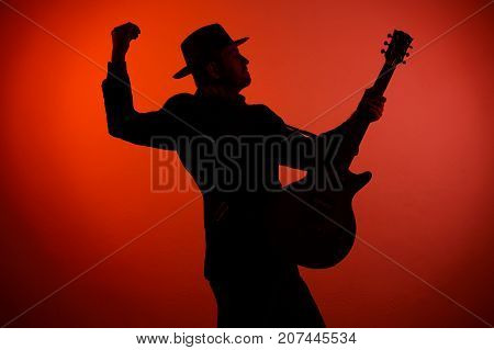 Silhouette Of A Musician Playing Instrument In A Hat