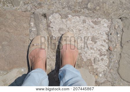 Female feet in blue jeans and ballet shoes on the cobblestone street