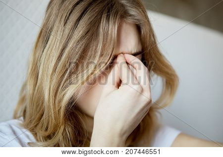Young woman sitting on bed with sinus pain.