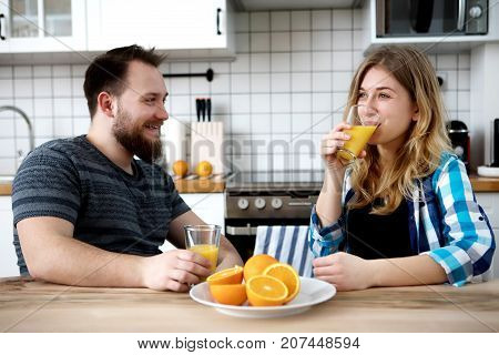 Young people drinking orange juice in kitchen.