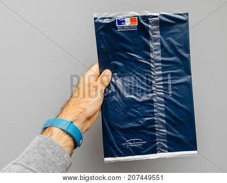 PARIS FRANCE - OCT 4 2017: Man holding against gray background envelope containing Taxe d'habitation (rates property tax) which is sent once per year to very household owner or people who rent a house apartment
