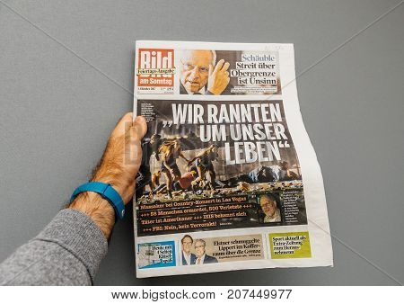 PARIS FRANCE - OCT 3 2017: Man holding Die Bild newspaper cover with socking title Pure Evil and photo after Las Vegas Strip shooting in United States
