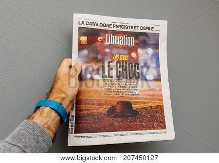 PARIS FRANCE - OCT 3 2017: Man holding French Liberation newspaper cover with socking title Pure Evil and photo after Las Vegas Strip shooting in United States