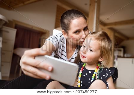 Beautiful young mother at home and her cute little daughter taking selfie with smart phone, mom kissing her on the head.