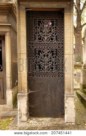 Old ornate iron door. Entrance to an old tomb, crypt at a cemetery.