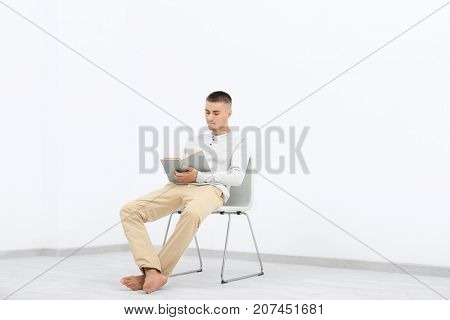 Young man with book resting on chair in empty room