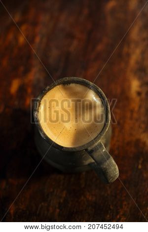 espresso coffee shot in vintage tin cup on old wooden table