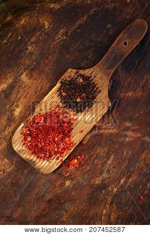 red hot chillies and chipotle jalapeno smoked chili flakes on textured woden background