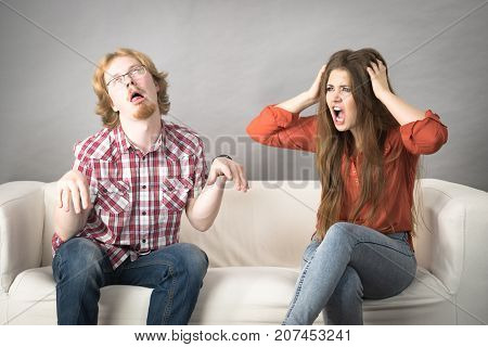 Man and woman having horrible fight while sitting on sofa. Friendship couple breakup difficulties and problems concept.