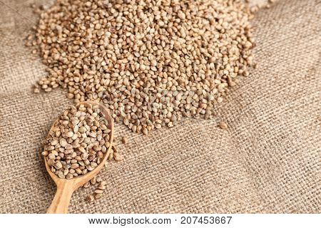 Spoon and heap of hemp seeds on sackcloth