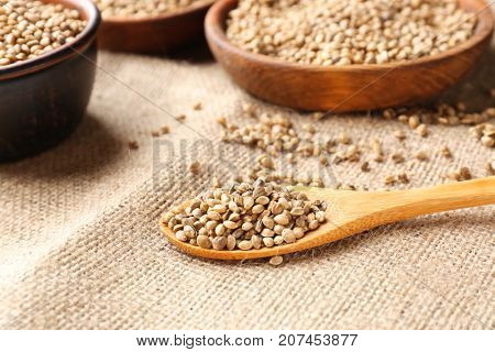 Wooden spoon with hemp seeds on sackcloth