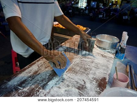 Man use tool clear powder made Chinese fried dough stick at night market of Thailand
