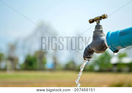 Save water.Water drop from water tap.Wasting water.Brass tap in nature background.