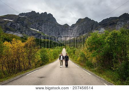 Hikers walk on a scenic road on Lofoten islands in Norway. Concept for friendship and relaxation.