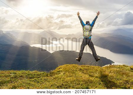 Man reaching summit and leaping for joy with raised and outstreched arms. He is looking towards spectacular coastal landscape with mountains and fjords during exhausting hiking travel trek. Hellandsnuten, Sandsfjord, Norway.