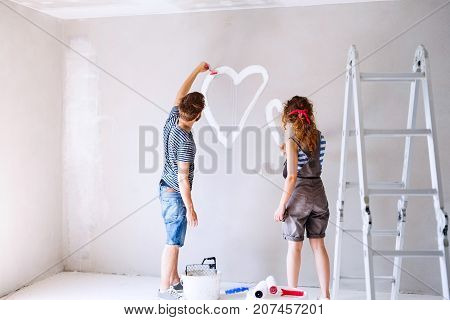 Beautiful young couple having fun and painting heart on the wall of their new house. Home makeover and renovation concept.