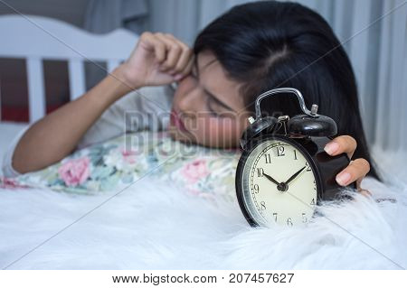 Asian girl on white bed wake up late look at alarm clock in morning