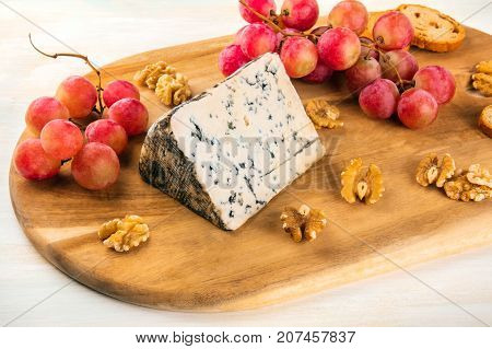 A photo of a piece of Gorgonzola with vibrant grapes, slices of bread, and nuts, on a light background with a place for text