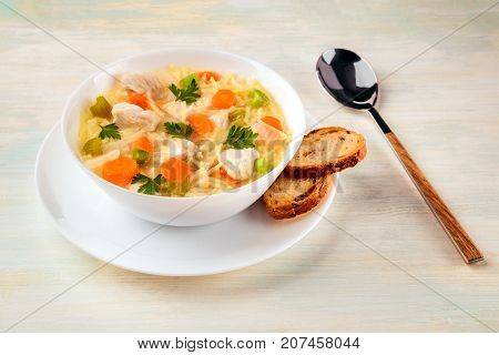 A photo of a plate of chicken, vegetables, and noodles soup, shot on a light texture with slices of bread and a spoon, selective focus