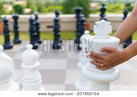 Women Hand Moving Big White Wood Chess On The Chessboard Floor With Blurred Black Wood Chess Backgro