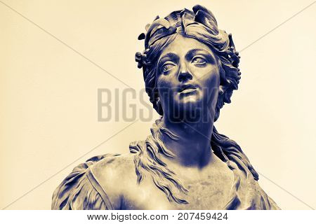 Ancient female statue of 18th century outdoor in park. Public domain. Nymph with a hoop of flowers, laurel leaves on her head. Beautiful photo for art calendars, prints, posters, design, cards. Stone.