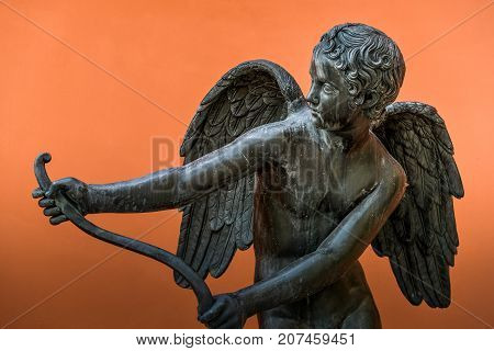 Outdoor ancient Cupid sculpture of 18th century from public park isolated on orange background. Public domain. Beautiful male body. Eros with wings and bow. Greek god of love for design, posters, prints.