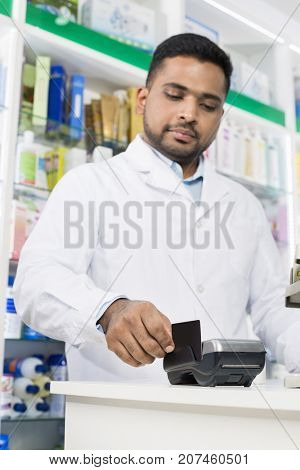 Young Pharmacist Swiping Credit Card On Reader