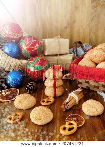 Biscuits with cinnamon surrounded by present boxes and Christmas attributes on a wooden background. Photo with special editing