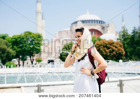 Young woman in a scarf with a backpack on the background of Aya Sofia and a fountain. Summer vacation, traveler