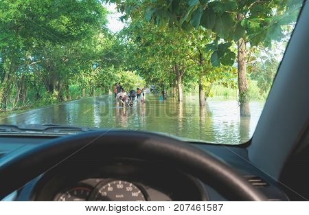Car driving in heavy rain on a flooded road. Car through flood water after hard rain.